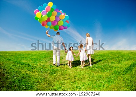 Happy family holding colorful balloons outdoor. Mom, dad and two daughters playing on  a green meadow.