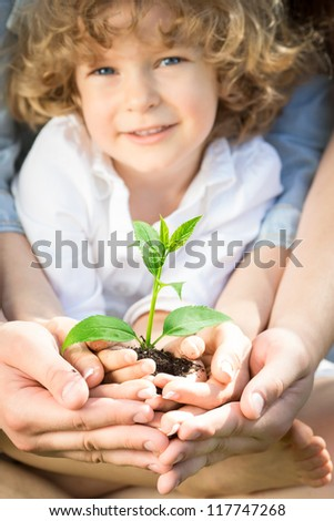 Happy family holding green young plant in spring outdoors. Ecology concept. Focus on sprout - stock photo