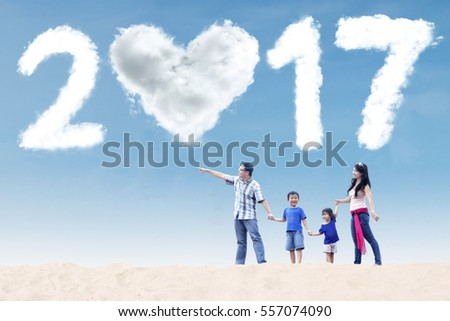 Happy family holding hands together and walking on the beach while looking at the sky with cloud 2017