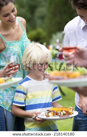 Happy family holding plates of barbecue - stock photo
