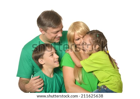 Happy family in a green clothes standing in studio - stock photo