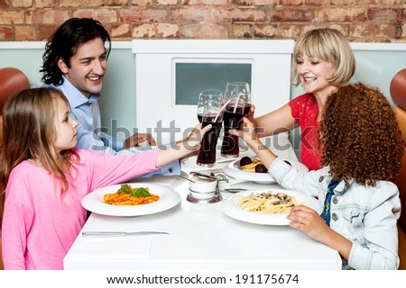 Happy family in a restaurant clinking their glasses - stock photo