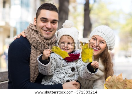 Happy family in at autumn park. A husband with his wife and daugher. Child is holding bright foliage. Shallow focus. Focus on man. - stock photo