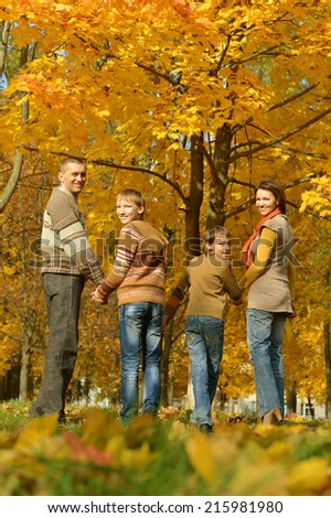Happy family in autumn park,back view - stock photo