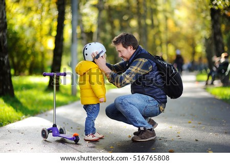 Happy family in autumn park. Middle age father helping his little son to put his helmet. Active toddler boy to ride a scooter. Child safety
