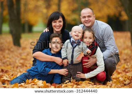 happy family in autumn park on yellow leaves
