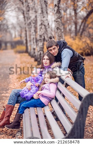 Happy family in autumn park. parents with children on a walk. Autumn walk, November