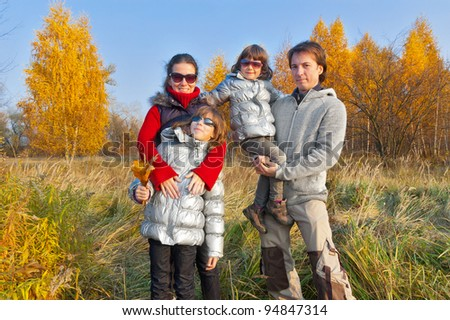 Happy family in autumn park. Smiling parents with kids having fun outdoodrs