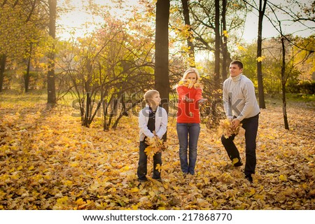 happy family in autumn park throws yellow leaves