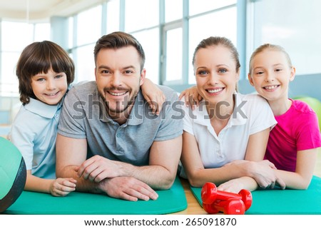 Happy family in fitness club. Happy sporty family bonding to each other while lying on exercise mat together   - stock photo