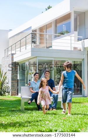 happy family in front of big modern new house outdoors, parents sitting on bench, children running on lawn grass smile - stock photo