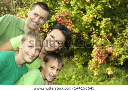 happy family in green shirts walking in the summer park