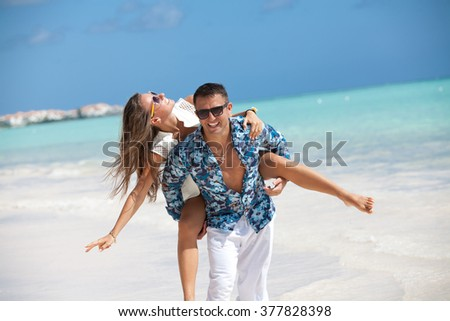 Happy family in love on beach summer vacations. Wife piggybacking on young husband playing and having fun in sunny tropical destination for travel holiday. - stock photo