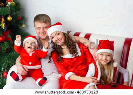 Happy family in Santa costumes waiting for the Christmas. Family look.