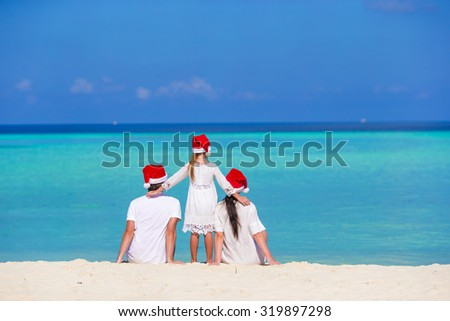 Happy family in Santa Hats on beach during Christmas vacation - stock photo