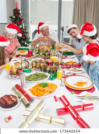 Happy family in santas hats enjoying Christmas dinner in the house - stock photo