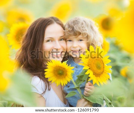 Happy family in spring field of beautiful sunflowers - stock photo