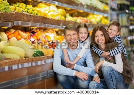 Happy family in store  - stock photo