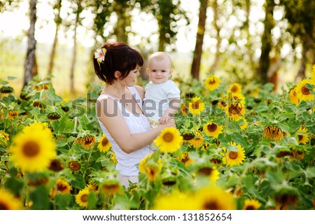 Happy family in summer field of beautiful sunflowers - stock photo
