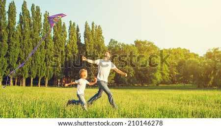 happy family in summer nature. Dad and son child flying a kite - stock photo