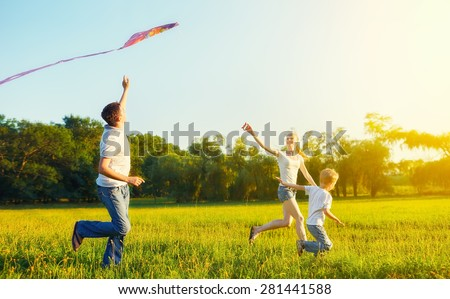 happy family in summer nature. Dad, mom and son child flying a kite - stock photo