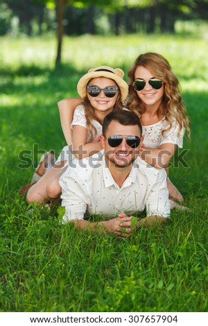 Happy family in summer park. happy young family spending time outdoor on a summer day. Family Lying In Pile Up On Grass Together