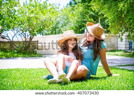 Happy family in the garden, beautiful mother with her little cute daughter sitting on fresh green grass on backyard, with pleasure spending time together - stock photo