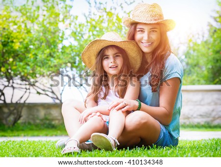Happy family in the garden, beautiful mother with her little cute daughter sitting on fresh green grass on a backyard, with pleasure spending time together - stock photo