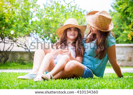 Happy family in the garden, beautiful mother with her little cute daughter sitting on fresh green grass in the backyard, with pleasure spending time together - stock photo