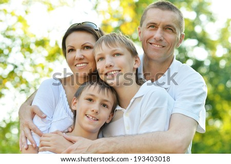 Happy family in the green in a summer park - stock photo