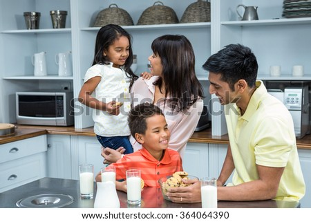 Happy family in the kitchen at home ready to eat biscuits - stock photo