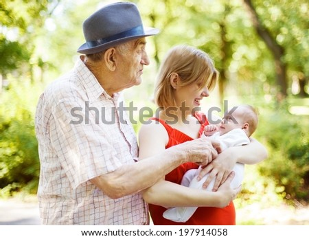 Happy family in the park. Grandfather, granddaughter and her baby are enjoying sunny day.  - stock photo