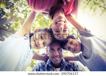 Happy family in the park huddling in circle on a sunny day