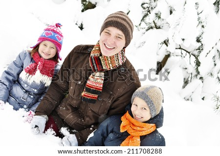 Happy family in the winter. Young father with two kids are sitting in the snow. It's snowing. - stock photo
