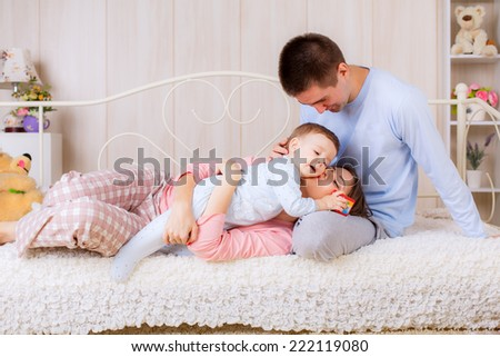 happy family in their pajamas on the bed  - stock photo