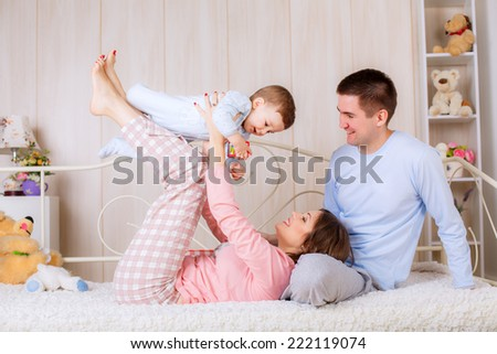 happy family in their pajamas on the bed in the nursery. doing gymnastics - stock photo