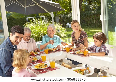 Happy family in three generations eating lunch together in summer - stock photo