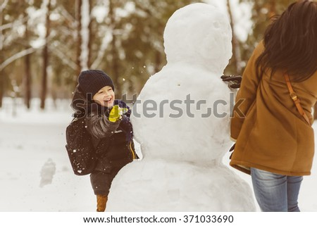 Happy family in warm clothing. Smiling mother and son play snowballs next to a snowman outdoor. The concept of winter activities - stock photo