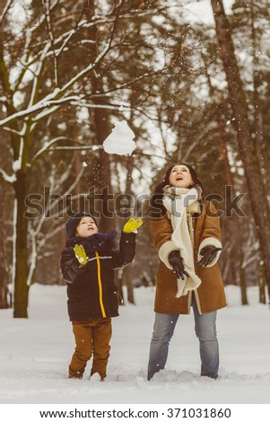Happy family in warm clothing. Smiling mother and son playing fun game outdoor. The concept of winter activities - stock photo