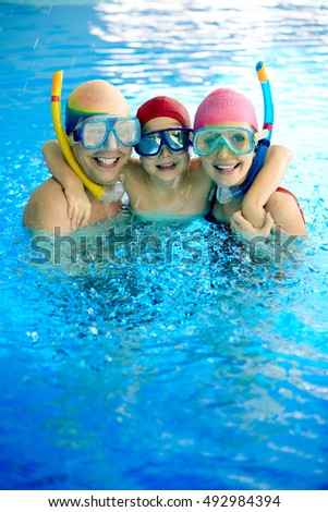 Happy family in water wearing scuba mask looking at camera