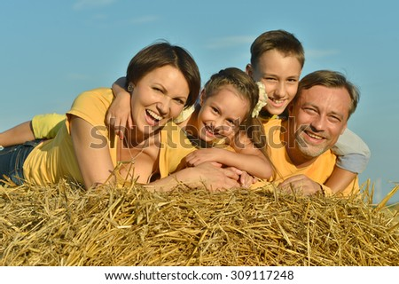 Happy family in wheat field in sunny day - stock photo