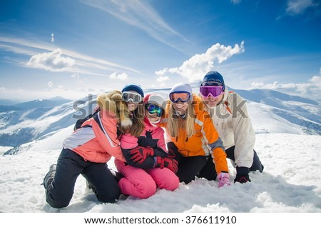 happy family in winter clothes lie on the snow at ski resort - stock photo