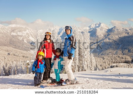Happy family in winter clothing at the ski resort, winter time - stock photo
