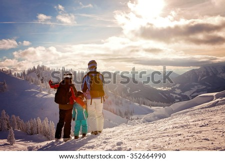 Happy family in winter clothing at the ski resort, winter time, watching at mountains in front of them - stock photo