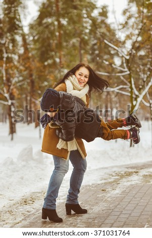 Happy family in winter clothing. laughing Mother and son playing fun game outdoor - stock photo