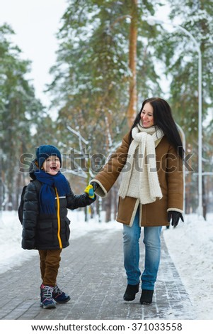 Happy family in winter clothing. Smiling mother and son walk at the park - stock photo
