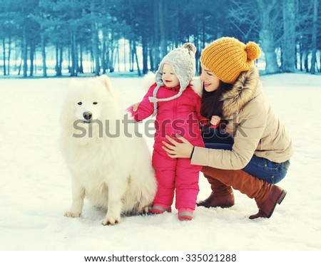 Happy family in winter day, mother and child walking with white Samoyed dog in park - stock photo