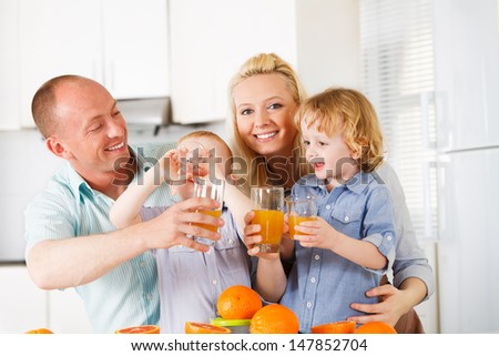 Happy family is drinking orange juice on their kitchen
