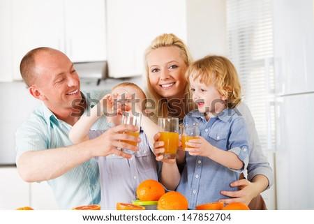 Happy family is drinking orange juice on their kitchen - stock photo