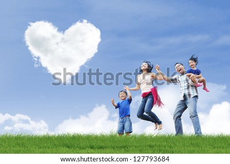 Happy family is having fun under love shape clouds in the park - stock photo